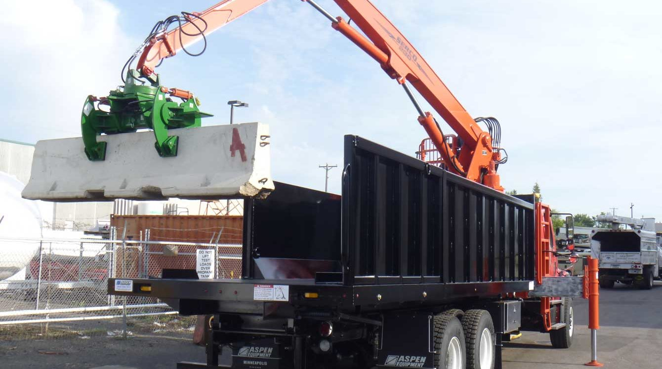 Serco 230B 23,000 lbs. capacity material grapple loader with jersey barrier handling attachment