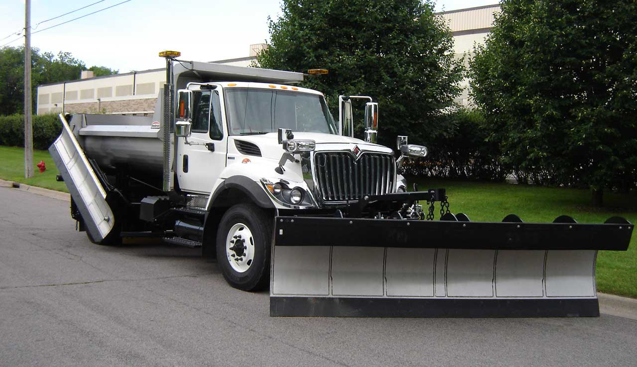 Single axle snow plow truck with stainless steel body, spreader, wing, and plow.