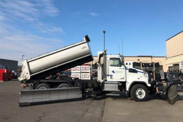 Tandem axle snow plow truck with stainless steel body, plow, wing salt/sand spreader