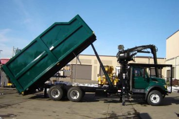 Serco 8500 series grapple loader with 22 ft Aspen Equipment dumping tree body