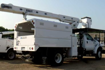 Behind-cab mounted 60.83 ft working height Versalift VO-255 forestry package with dumping chip body
