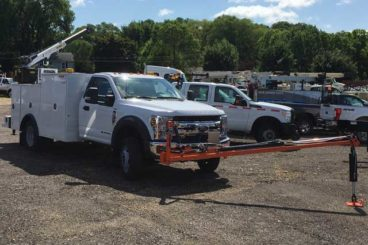 Mechanic body converted into a sign truck with service crane, sign storage, and post puller
