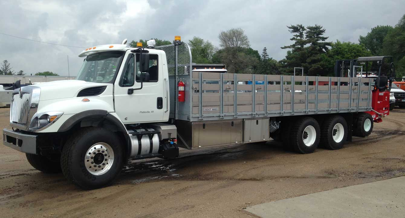Sauber Mfg 24 ft galvanized flatbed with drop stake sides and Moffett rear-mounted forklift