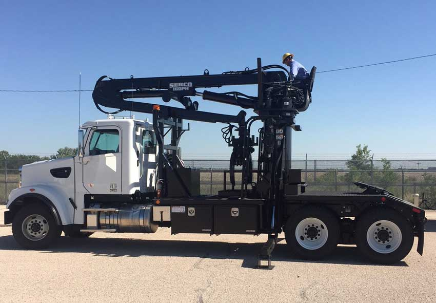 Behind-cab mounted Serco 8500 loader with pole grapple and flatbed body