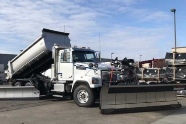 Tandem axle plow truck with stainless steel body, plow, wing, and salt/sand spreader